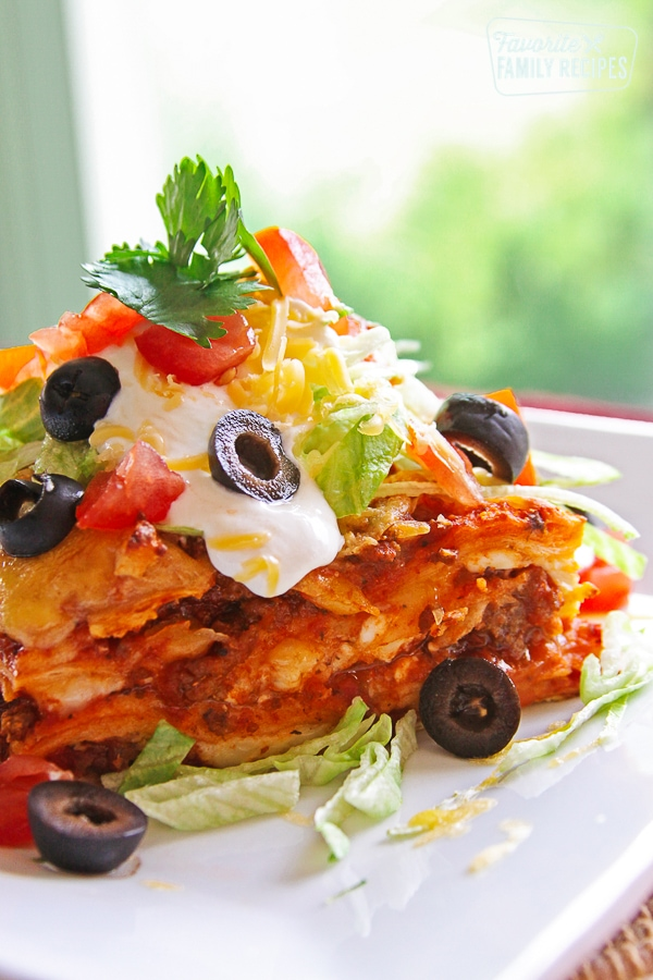 A piece of Mexican Lasagna topped with cheese, olives, lettuce, and cilantro on a white plate.