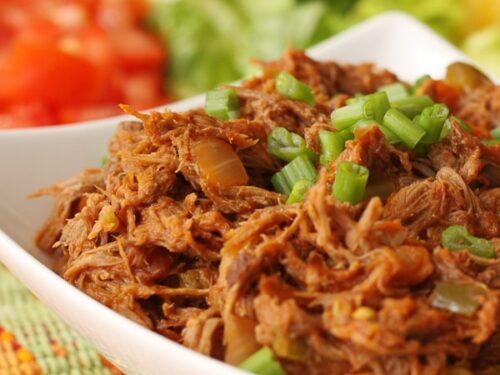 Crock Pot Mexican Shredded Beef served in a white bowl on a colorful placemat with chopped tomatoes, lettuce, and shredded cheese in the background