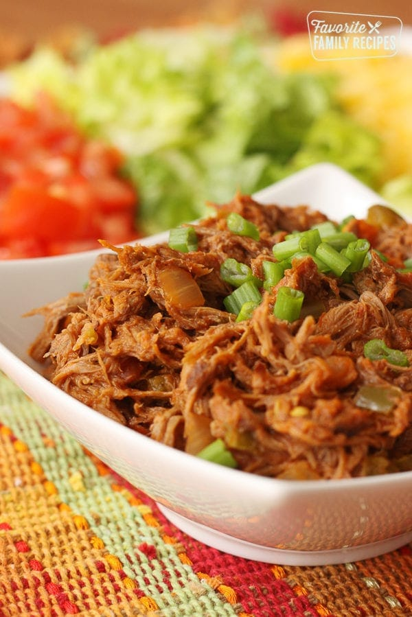 Crock Pot Mexican Shredded Beef served in a white bowl on a colorful plate with Mexican food