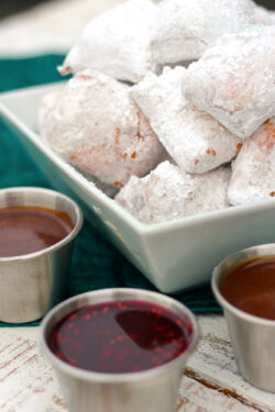 New Orleans Mini Beignets covered in powdered sugar with three dipping sauces on the side.