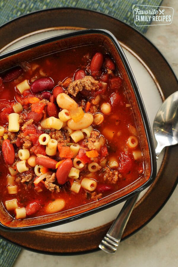 Our Version of Olive Garden's Pasta E Fagioli Soup in a square bowl on a plate with a spoon on the side.