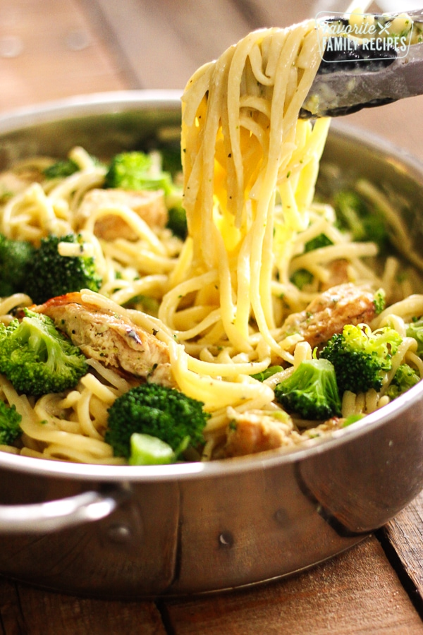 One Pot Creamy Garlic Noodles with tongs holding up noodles from the pot.