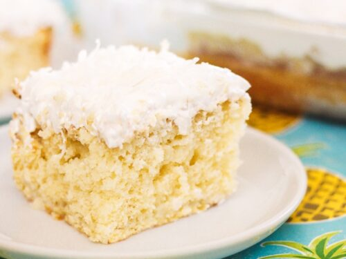 A slice of Pina Colada Poke Cake on a white plate