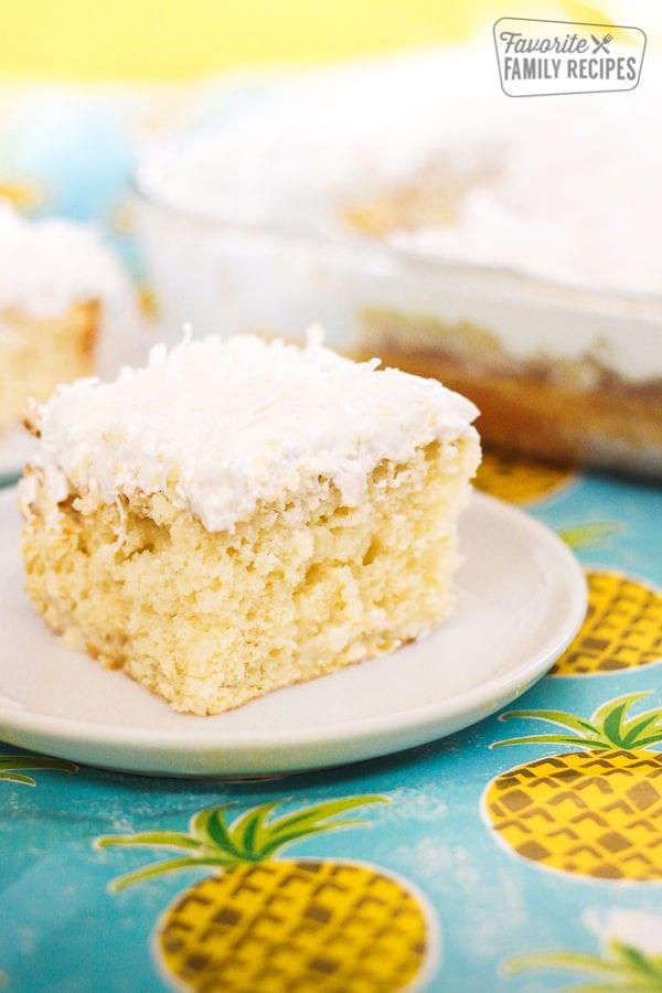 A slice of Pina Colada Poke Cake on a white plate