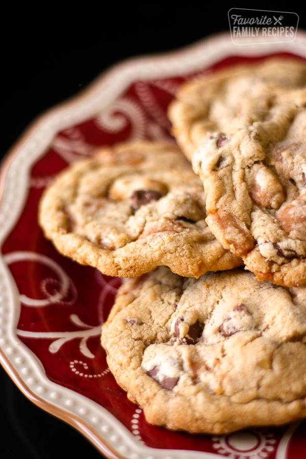 Turtle Cookies with chocolate chips, pecans, and caramel bits served on a red decorative plate.