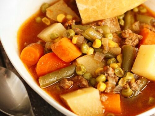 Crock pot vegetable beef soup in a white square bowl with bread on the side