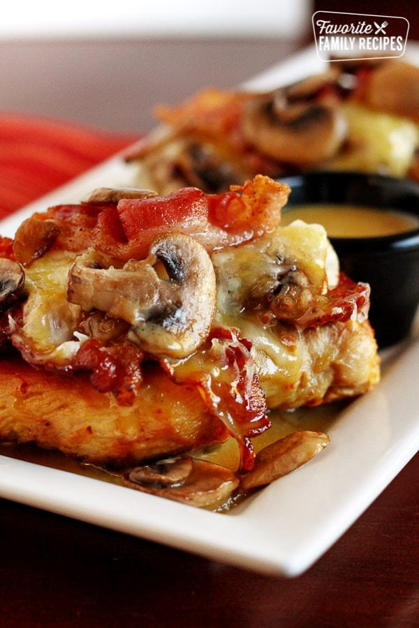 Outback's Alice Springs Chicken topped with bacon and mushrooms on a white tray with a side of sauce.