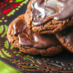 3 Andes Mint cookies stacked on a metal Christmas plate.