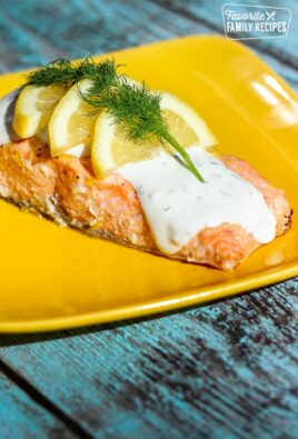Baked Lemon Salmon covered Tzatziki Sauce,3 lemon slices, and parsley on a yellow plate.