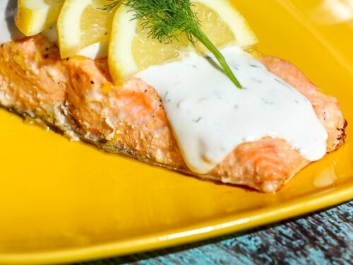 Baked Lemon Salmon covered Tzatziki Sauce,3 lemon slices, and parsley on a yellow plate.