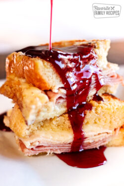 Baked Monte Cristo French Toast with dark red Syrup Pouring on Top