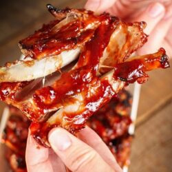 Piece of blue ribbon bbq ribs being held up in someone's hands