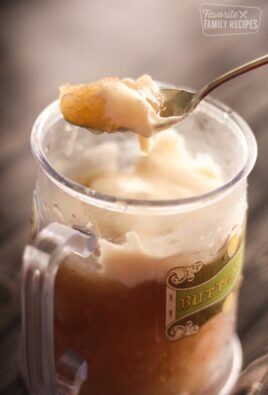 Frozen Butterbeer in a glass mug and a spoon scooping some out.