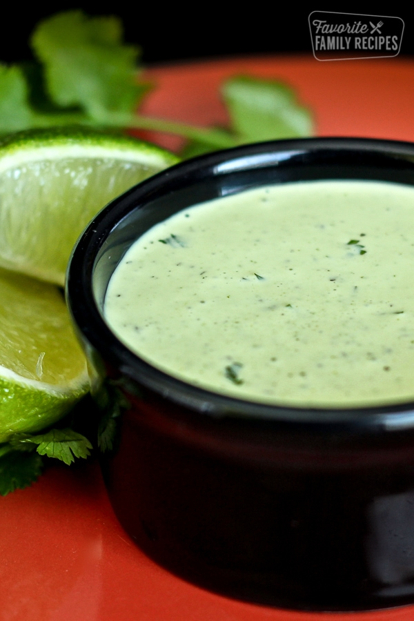 Cafe Rio Cilantro Ranch Dressing in a small black bowl with sliced limes in the background.