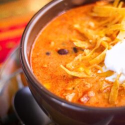 Cafe Zupas Chicken Enchilada Chili with tortilla strips and sour cream in a bowl.