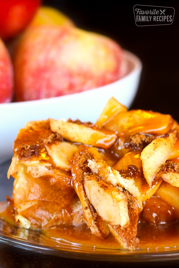 Caramel Apple French Toast on a plate with a bowl of apples in the background.