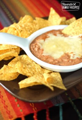 Cheater Restaurant Style Refried Beans in a white bowl surrounded by tortilla chips.