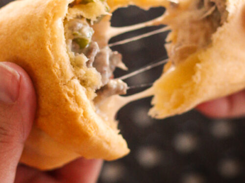 Cheesesteak Crescent Roll being torn into two pieces.