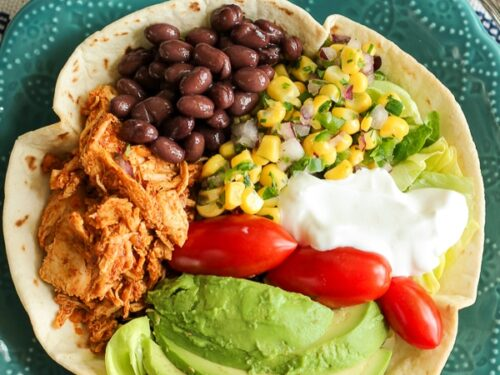Chicken Taco Salad in a Tortilla Bowl with corn, beans, avocado, tomatoes, and sour cream in a blue bowl