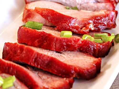 6 slices of Chinese BBQ Pork with green onions on a white tray