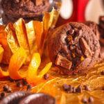 Chocolate orange cookies with an orange peel and chocolate shavings on the side.