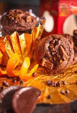 Chocolate orange cookies with an orange peel and chocolate shavings on the side.