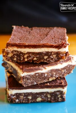3 Coconut Pecan Nanaimo Bars stacked on top of each other on a blue plate