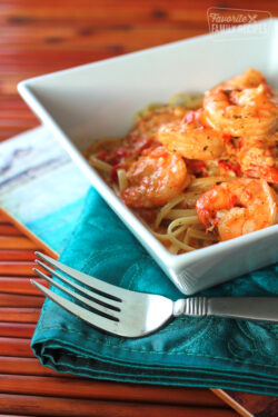 Creamy Cajun Shrimp Pasta in a white bowl with a fork on the side