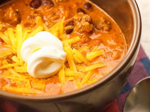 Close up of Creamy Italian Sausage Chili with a dollop of sour cream in a bowl.