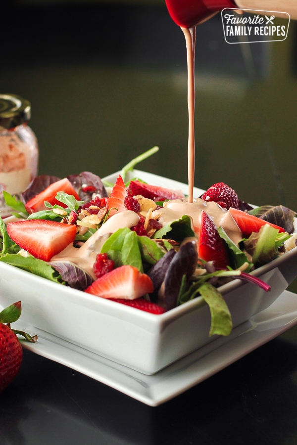 Creamy Strawberry Balsamic Dressing being poured onto a strawberry salad.