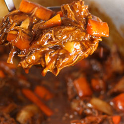 Danish Goulash beef and carrots in a bowl and on a spoon