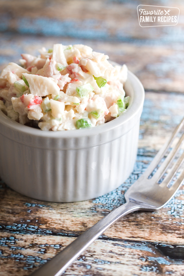 Easy crab salad in a small white bowl with a fork on the side.