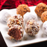 Easy Chocolate Truffle Balls covered in nuts and powdered sugar on a white tray