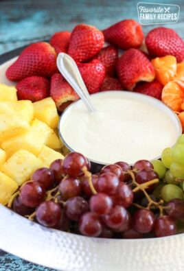Easy Fruit Dip in a bowl surrounded by strawberries, oranges, pineapples, red grapes and green grapes