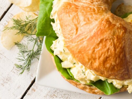 Overhead view of Egg Salad Sandwich on a plate with chips on the side.