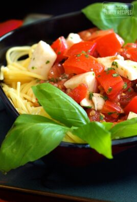 Close up of Fresh Tomato and Basil Pasta in a black bowl.