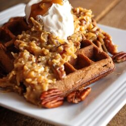 German Chocolate Waffles topped with Praline Pecan Syrup and whipped cream on a white plate.