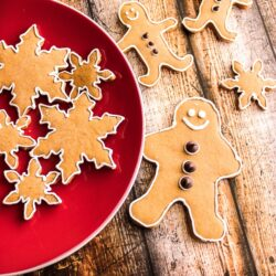 Gingerbread cookies decorated as snowflakes and gingerbread men on a red plate