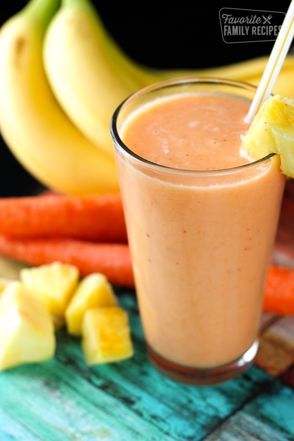 Golden Detox Smoothie in a tall glass with pineapples, bananas, and carrots on the side.