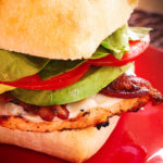 Close up of a Grilled Chicken Sandwich with Spicy Aioli Mayo on a red plate
