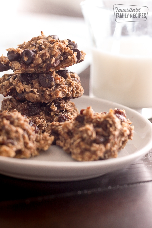 Guilt Free Oatmeal Cookies stacked on a white plate with a glass of milk in the background.