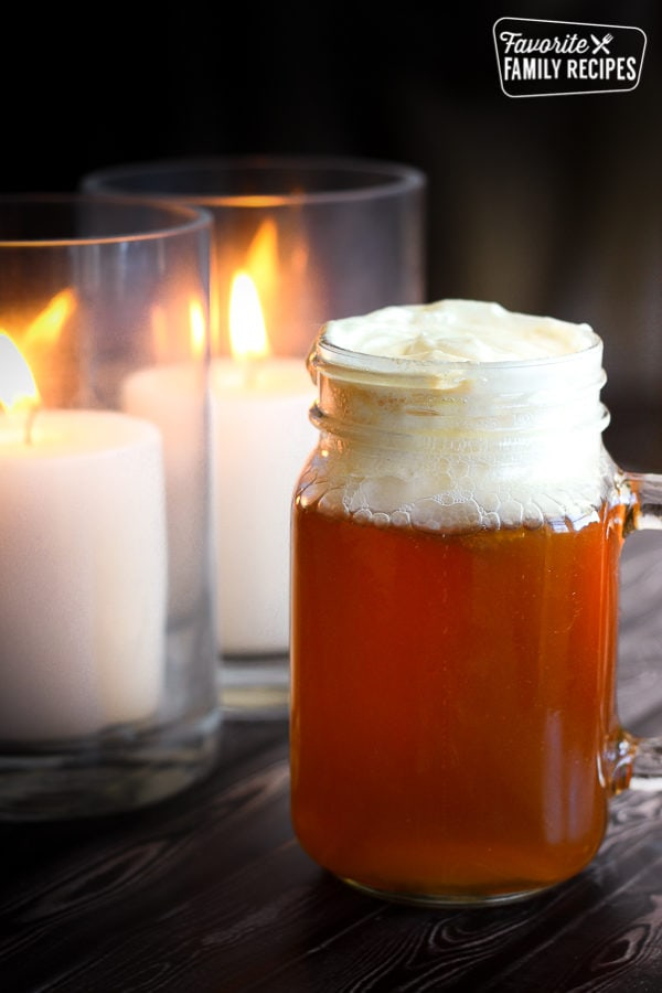 Butterbeer from the Wizarding World of Harry Potter with two candles in the background.