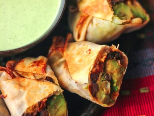 Healthy Baked Fiesta Avocado Egg Rolls on a plate with a dipping sauce on the side.