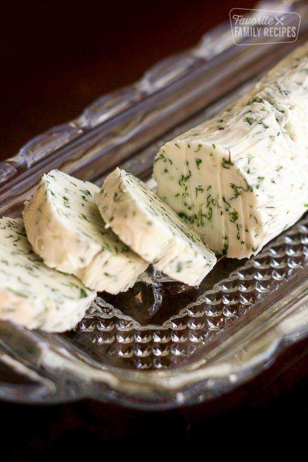 Slices of herbed butter on a glass butter dish