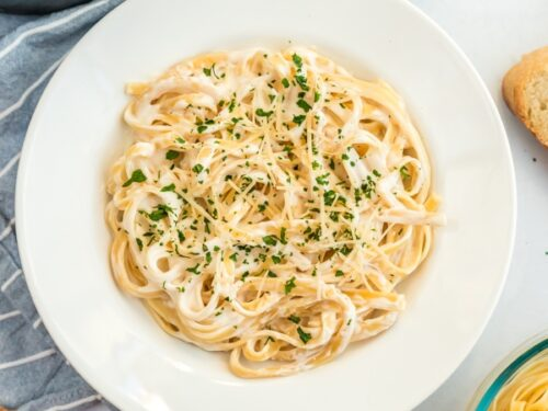 A large bowl of pasta with Alfredo sauce, parmesan and parsley