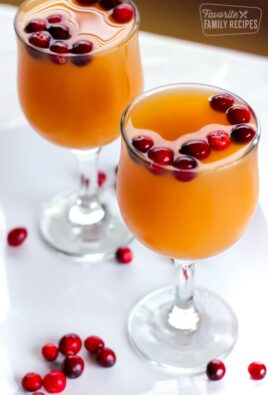 Two stemmed glasses filled with Homemade Sparkling Cider topped with fresh cranberries