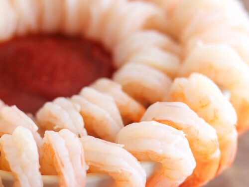 A double cocktail shrimp ring with cocktail sauce in the center