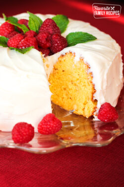 Lemon Bundt Cake topped with raspberries with a slice cut out.