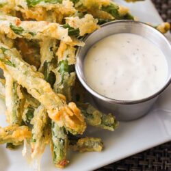Lightly Fried Green Beans with a side of Lemon Dill Dip on a white plate.