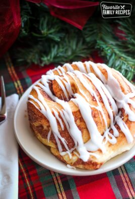 Lion House Cinnamon Roll on a white plate on top of a christmas table cloth.